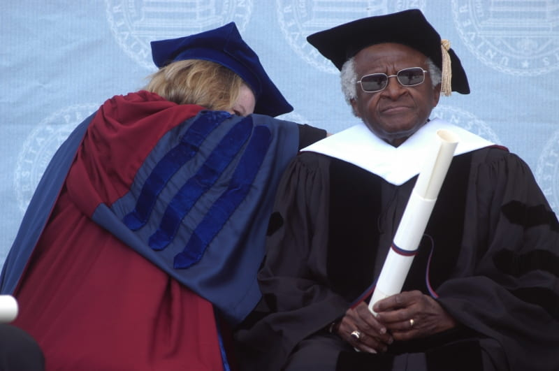 Desmond Tutu at the University of Pennsylvania in 2004 wearing academic gown and mortar board and holding a long white scroll while a woman in academic robes appears to be adjusting something on his back.