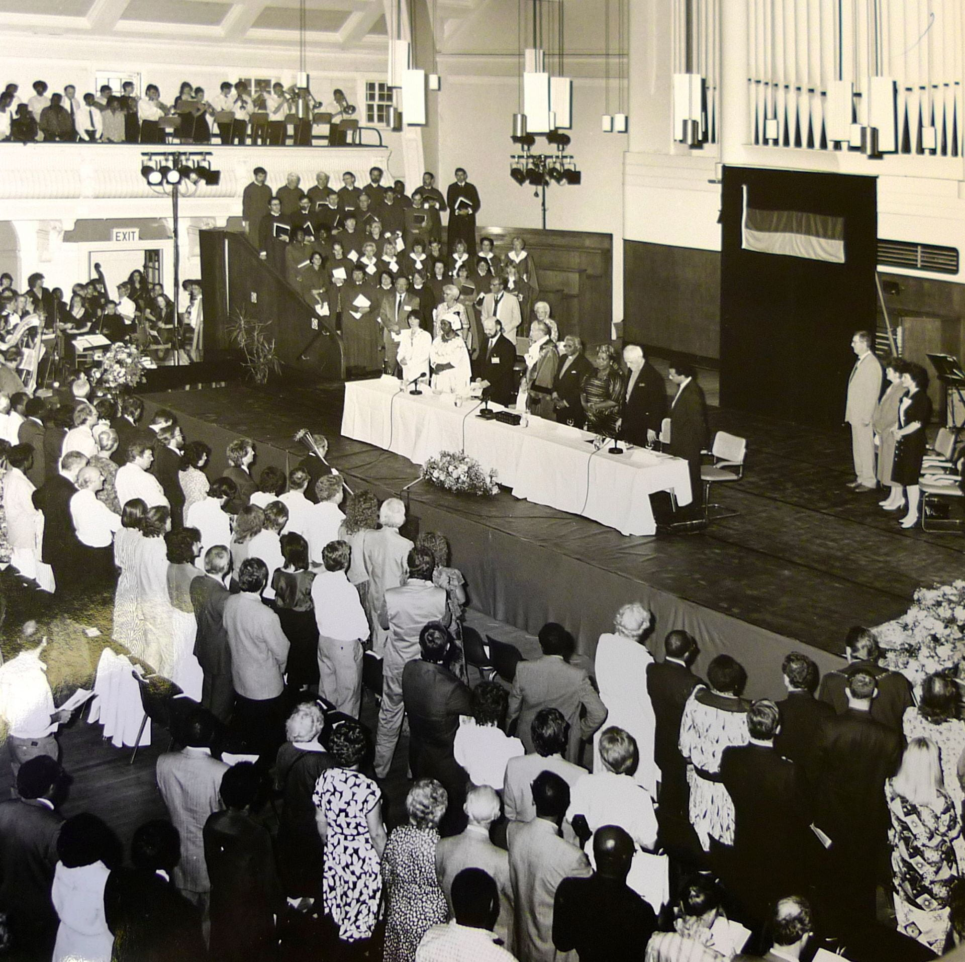 Black and white photograph of the Great Hall of Goldsmiths on May 4th 1990 taken from balcony looking down at stage in front of the organ where his most reverend Desmond Tutu is receiving the honorary freedom of Lewisham. Lewisham Council dignatories, local MP and Goldsmiths' College staff and students present.