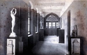 Black and white photograph of a corridor of the Blomfield building of Goldsmiths' College in 1908 with classical statues on plinths against the walls.