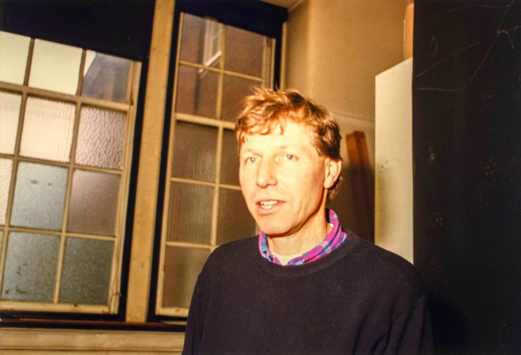 A portrait of Nigel Perkins in sweater and open necked shirt taken in studio of Goldsmiths main building in 1996.