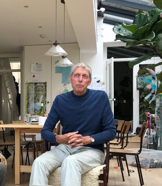 Portrait of Nigel Perkins in September 2019 sitting in chair, hands clasped and looking as though a thought has come into his head and he is about to say something. He's also wearing one of his characteristic turtle neck sweaters.