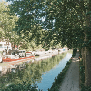 narrow river with boats parked on the left and a narrow path with overhanging trees to the right