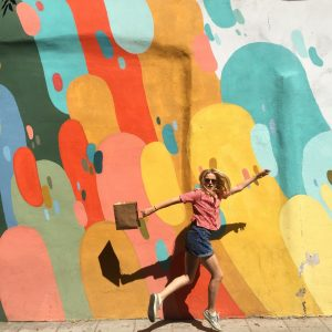 a young blonde woman jumping in the air against the backdrop of a multi-colour painted wall