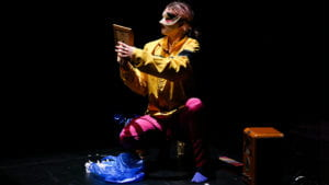 A figure wearing a yellow top, pink trousers and a decorative eye mask crouches down looking at a picture in a frame