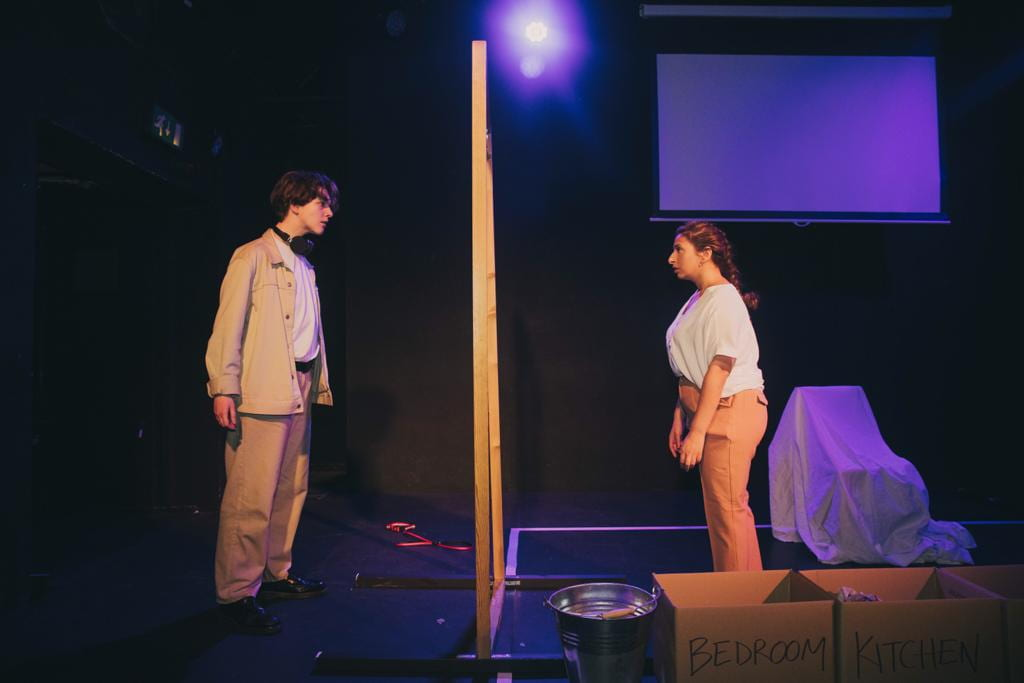 Liv, wearing a beige shirt and trousers, stands stage right looking through a large wooden frame into the eyes of another performer, also wearing beige