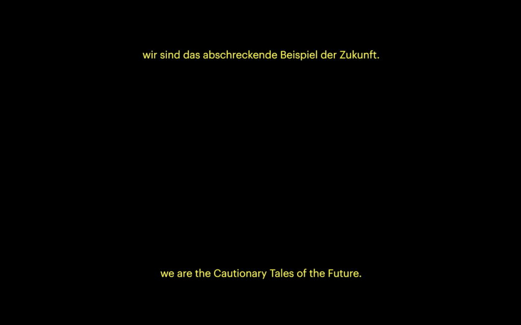 """A still of a black video screen with subtitles in yellow sans serif text at the top and bottom. The top layer of subtitles are in German. The bottom layer reads """"we are the Cautionary Tales of the Future""""."""