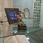 book, magnifying glass, digital image display and plastic hand in glass display case