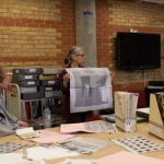 Woman holding up a newsprint poster behind table covered in slide files, magazines and newsprint publications surrounded by workshop participants.