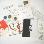 one of the Mail Art envelopes unpacked to show letter with 4 graphic works