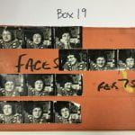 Horizontal photograph of strips of black and white negatives of of photos of a white dark haired woman with glasses, stuck on an orange cardboard folder with faded masking tape