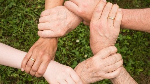 Image shows people holding their hands in unity