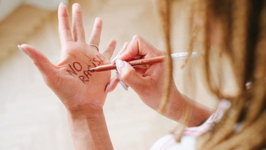 Image showing a person writing ' no racism' on their hand