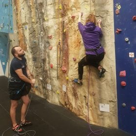 Image shows a student at the climbing wall