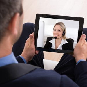 man holding a screen on which a woman appears by video conferencing