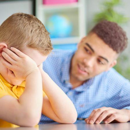 teacher supporting an upset boy
