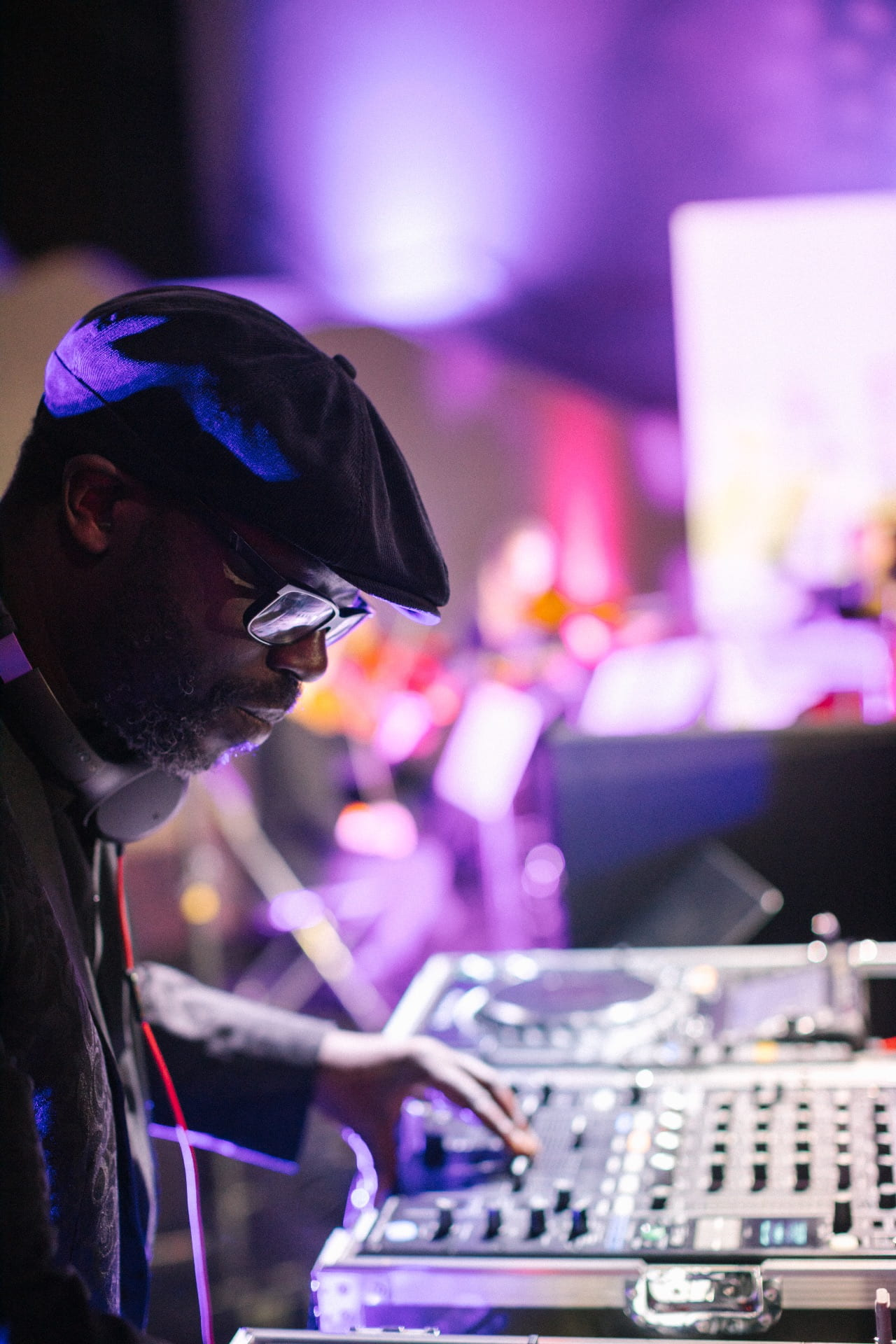 image of Peter adjure playing music from DJ deck with purple lighting around him
