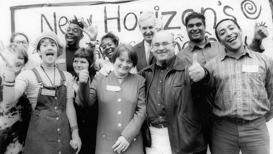 Black and white photo of New Horizon group members smiling and with their thumbs up posing in front of a hand made New Horizon banner. Journalist Jon Show positioned centre back.