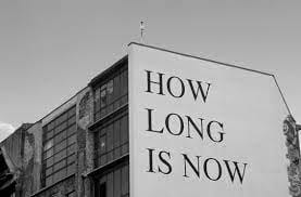 image of how long is now painted on a very large mural wall, on the side of a building. Black text on white background