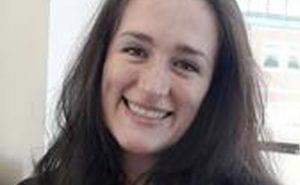 A headshot of Deljana smiling and looking straight at camera.