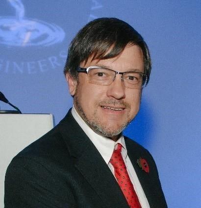 A headshot of John smiling and looking straight at camera