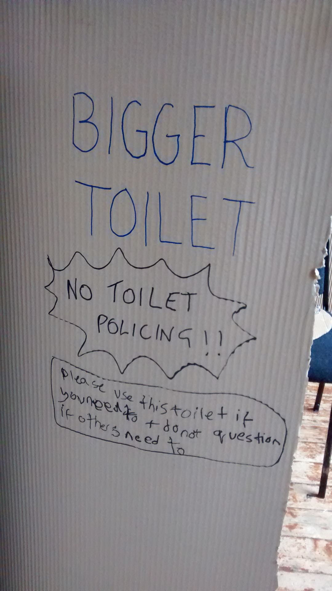 A photo of a large piece of brown corrugated cardboard. On it, a person taking part in an 'Around the Toilet' workshop has written 'TOILET. NO TOILET POLICING. Please use this toilet if you need to and don't question if others need to.'