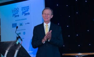 Mike stands clapping on stage at the Loo of The Year awards 2019.