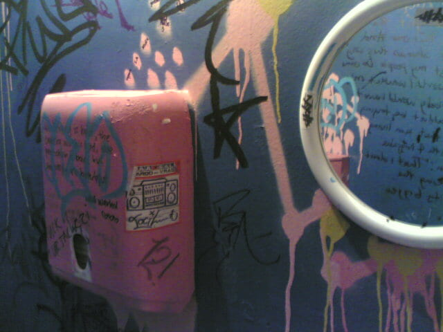 Toilet Wall showing hand dryer and mirror. Dark blue wall and hand dryer (painted poorly in pink) covered in graffiti including reflection in mirror.