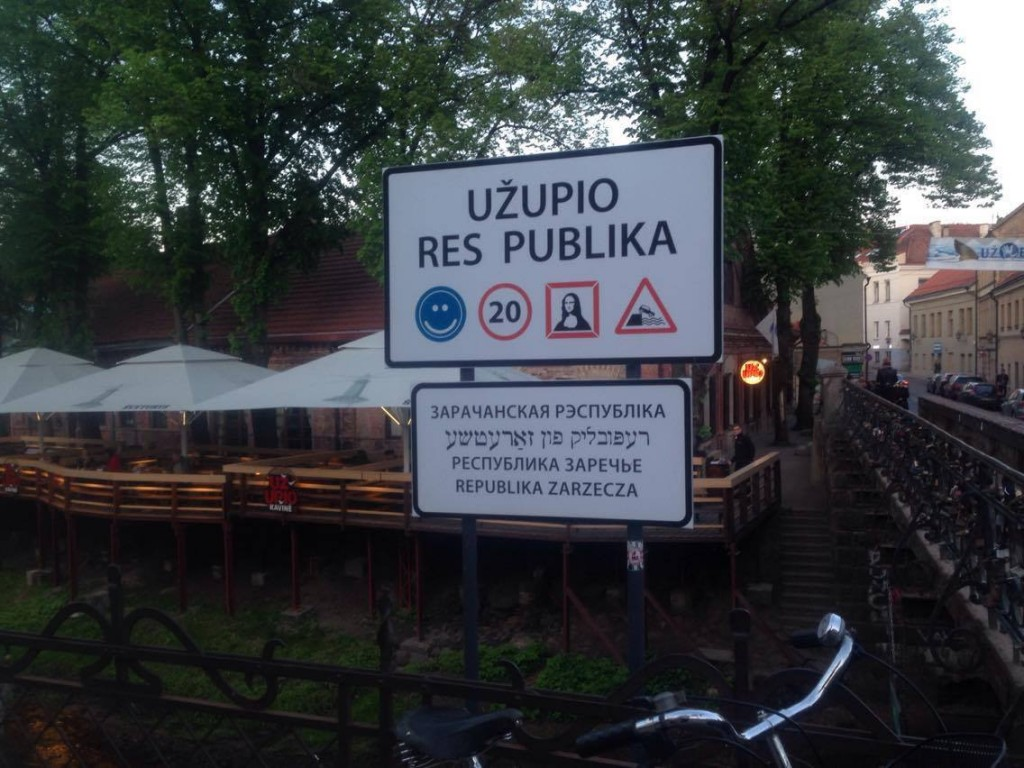 The welcome sign for the Republic of Užupis pronounced in several different languages and universal symbols announcing their rules and intentions: smiling, no speeding, and experience the art. Photo: Emily Mundzic