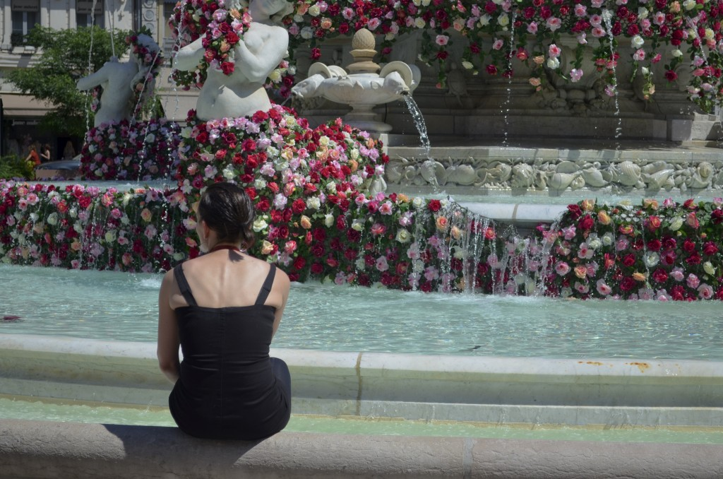 A member of the prostitutes' manifestation in Lyon, France, takes her shoes off to dip her feet in the fountain before joining the crowd.